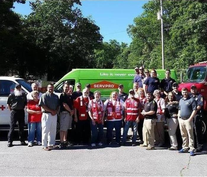 SERVPRO and the American Red Cross employees standing in front of a fire truck